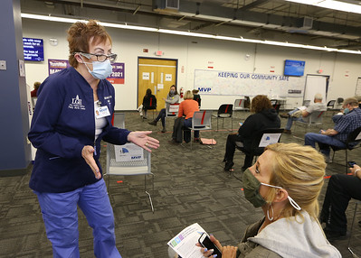 Volunteers at Lowell General Hospital's vaccination site at Cross River Center in Lowell. Retired LGH nurse Michelle Ratty, R.N., of Tyngsboro, chats with people as she monitors the room where people wait 15 minutes after receiving their vaccinations. Lisa Loiselle of Lowell, right, who'd just gotten her first dose of Pfizer, happens to be Ratty's second cousin by marriage, and they're buddies. JULIA MALAKIE/LOWELLSUN