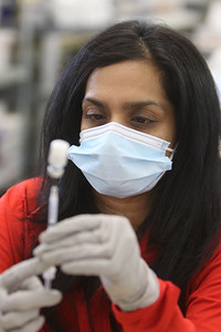 Volunteers at Lowell General Hospital's vaccination site at Cross River Center in Lowell. Volunteer Varsha Karanth, M.D., of Andover, draws Pfizer vaccine into syringes.  JULIA MALAKIE/LOWELLSUN