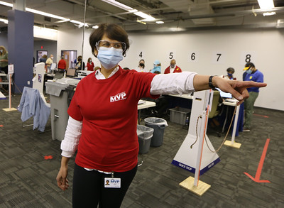 Volunteers at Lowell General Hospital's vaccination site at Cross River Center in Lowell. Ajita Bhat of Andover, one of about a dozen volunteers with Chinamaya Mission Boston, directs people to vaccination stations.  JULIA MALAKIE/LOWELLSUN