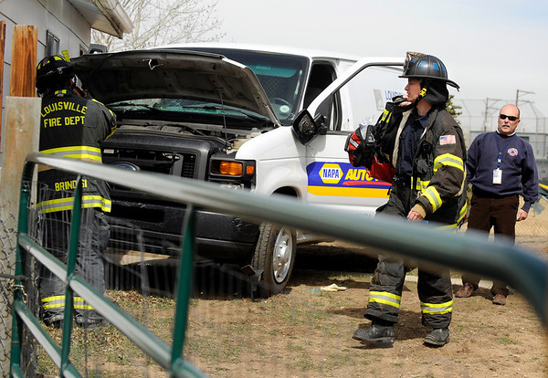 """CarCrash001.JPG Louisville firefighters examine the scene after a car crashed into a storage shed, through Miners Field and into a garage on Friday, March 25, on 96th Street in Louisville. For a video of the crash go to  <a href=""""http://www.dailycamera.com"""">http://www.dailycamera.com</a><br /> Jeremy Papasso/ Camera"""