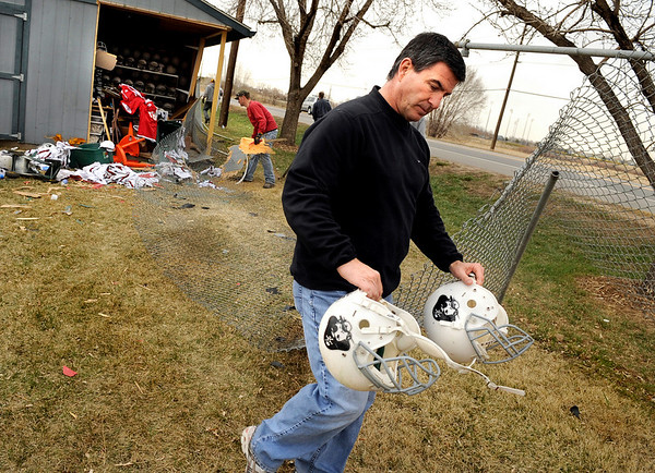 "CarCrash008.JPG Louisville Pirates assistant football coach Michael Calo carries away damaged football equipment after a van crashed into a storage shed, through Miners Field and into a garage on Friday, March 25, on 96th Street in Louisville. For a video of the crash go to  <a href=""http://www.dailycamera.com"">http://www.dailycamera.com</a><br /> Jeremy Papasso/ Camera"