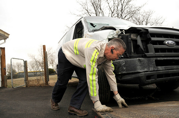 "CarCrash006.JPG Cozy Corner Towing employee Dennis Seay, works to put a van on to a flatbed after the driver crashed into a storage shed, through Miners Field and into a garage on Friday, March 25, on 96th Street in Louisville. For a video of the crash go to  <a href=""http://www.dailycamera.com"">http://www.dailycamera.com</a><br /> Jeremy Papasso/ Camera"