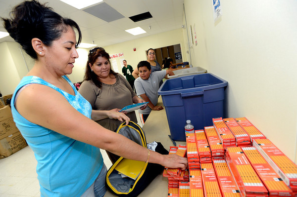 "Volunteers Norma Medrano, left and Valentina Contreras organize and fill backpacks full of  school supplies as part of the Crayons to Calculators drive in Boulder on Thursday July 19, 2011. For more photos and a video of the drive go to  <a href=""http://www.dailycamera.com"">http://www.dailycamera.com</a> <br /> Photo by Paul Aiken / The Camera"