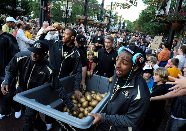 "University of Colorado football players Paul Richardson, left, Jered Bell and Will Jefferson, right, pass out mini Buff footballs to the crowd during the Buff Stampede on Friday, Sept. 3, on the Pearl Street Mall.<br /> Jeremy Papasso/ Camera<br /> <br /> For video of the stampede and a photo gallery go to  <a href=""http://www.dailycamera.com"">http://www.dailycamera.com</a>"