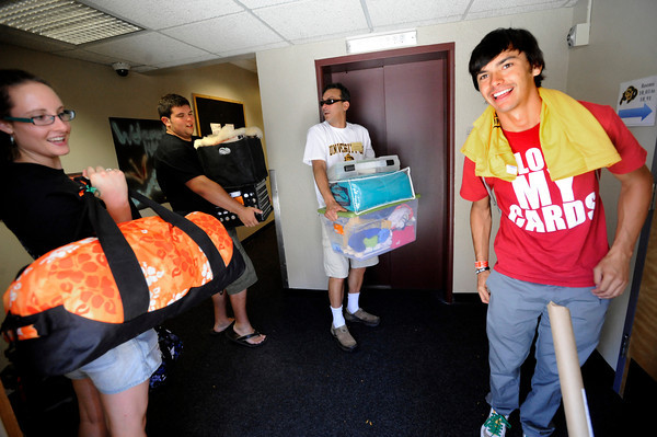 "Oscar Gates can find the card that will get him through the security door at Hallet Hall during freshman move in day on Tuesday August 16, 2011.. Helping his move in is his from left to right volunteers Jessica Connelly and Andrew Trujillo and his dad Kent Gates. The family is from San Francisco. FOR MORE PHOTOS FROM MOVE IN DAY GO TO  <a href=""http://WWW.DAILYCAMERA.COM"">http://WWW.DAILYCAMERA.COM</a> AND COLORADODAILY.COM<br /> Photo by Paul Aiken / The Camera / 8/ 16/ 11"