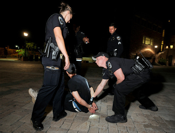 """University of Colorado police officer Emily Smyly, left, Sergeant Adam Trojanowski, middle, and officer Mike Deloncker, right, work together to handcuff Kevin McClellan, 18, of Boulder, after a foot chase during a patrol on Thursday, Sept. 6, on the CU campus in Boulder. McClellan was ticketed twice in one night on two seperate incidents. For more photos and video of the CU police in action go to  <a href=""""http://www.dailycamera.com"""">http://www.dailycamera.com</a><br /> Jeremy Papasso/ Camera"""