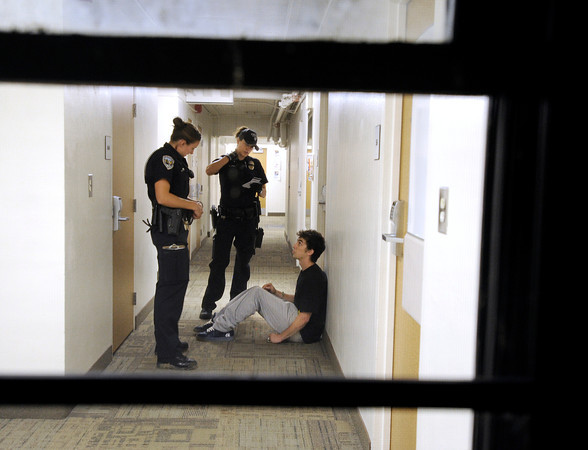 """University of Colorado police officer Emily Smyly, left, and officer Amy Pratt confront a student suspected of drinking in Libby Hall during a patrol on Thursday, Sept. 6, on the CU campus in Boulder. For more photos and video of the CU police in action go to  <a href=""""http://www.dailycamera.com"""">http://www.dailycamera.com</a><br /> Jeremy Papasso/ Camera"""
