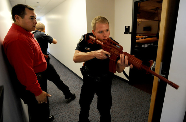 """Instructor Ken Pacheco, left, monitors Mike Deloncker, right, among other officers participating in a training exercise.<br /> New University of Colorado police were trained in an """"active harmer"""" scenario, similar to a Virginia Tech shooting situation.<br /> For a video of the CU Police training exercise, go to  <a href=""""http://www.dailycamera.com"""">http://www.dailycamera.com</a>.<br /> December 28, 2011 / Cliff Grassmick"""