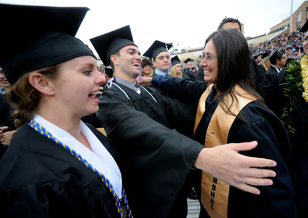 "Valerie Eric, left, watches Thomas Quaas hug Peggy Gordon after the CU graduation ceremony on Friday.<br /> The ceremony will honor candidates for 6,237 degrees, including 4,830 bachelor's degrees, 994 master's degrees, 162 law degrees and 251 doctoral degrees for spring and summer.<br /> The number of degree applications for the University of Colorado is the largest in the school's history, and comes four years after the record-setting freshman class of fall 2008. That year, 5,833 freshmen enrolled, exceeding the previous record-setting class of 2006 that enrolled 5,617 freshmen. For more photos and a video, go to  <a href=""http://www.dailycamera.com"">http://www.dailycamera.com</a>.<br /> Cliff Grassmick / May 11, 2012"