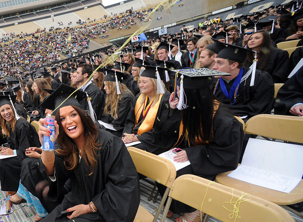 """Elle Daoust celebrates with silly string near the end of the ceremony.<br /> The ceremony will honor candidates for 6,237 degrees, including 4,830 bachelor's degrees, 994 master's degrees, 162 law degrees and 251 doctoral degrees for spring and summer.<br /> The number of degree applications for the University of Colorado is the largest in the school's history, and comes four years after the record-setting freshman class of fall 2008. That year, 5,833 freshmen enrolled, exceeding the previous record-setting class of 2006 that enrolled 5,617 freshmen. For more photos and a video, go to  <a href=""""http://www.dailycamera.com"""">http://www.dailycamera.com</a>.<br /> Cliff Grassmick / May 11, 2012"""