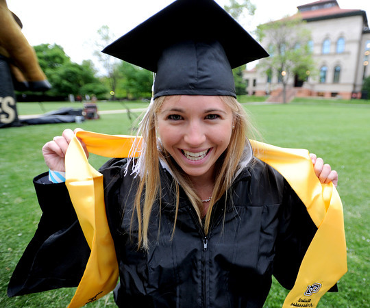 "Megan Collins gets ready for graduation while waiting in Norlin Quad Friday morning.<br /> The ceremony will honor candidates for 6,237 degrees, including 4,830 bachelor's degrees, 994 master's degrees, 162 law degrees and 251 doctoral degrees for spring and summer.<br /> The number of degree applications is the largest in the school's history, and comes four years after the record-setting freshman class of fall 2008. That year, 5,833 freshmen enrolled, exceeding the previous record-setting class of 2006 that enrolled 5,617 freshmen.<br /> For more photos and a video of graduation, go to  <a href=""http://www.dailycamera.com.com"">http://www.dailycamera.com.com</a>.<br />  Cliff Grassmick / May 11, 2012"