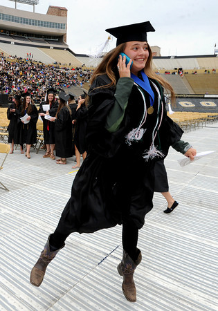 "Ashley Basta is jumping for joy while talking to her family on the phone during graduation on Friday.<br /> The ceremony will honor candidates for 6,237 degrees, including 4,830 bachelor's degrees, 994 master's degrees, 162 law degrees and 251 doctoral degrees for spring and summer.<br /> The number of degree applications for the University of Colorado is the largest in the school's history, and comes four years after the record-setting freshman class of fall 2008. That year, 5,833 freshmen enrolled, exceeding the previous record-setting class of 2006 that enrolled 5,617 freshmen. For more photos and a video, go to  <a href=""http://www.dailycamera.com"">http://www.dailycamera.com</a>.<br /> Cliff Grassmick / May 11, 2012"