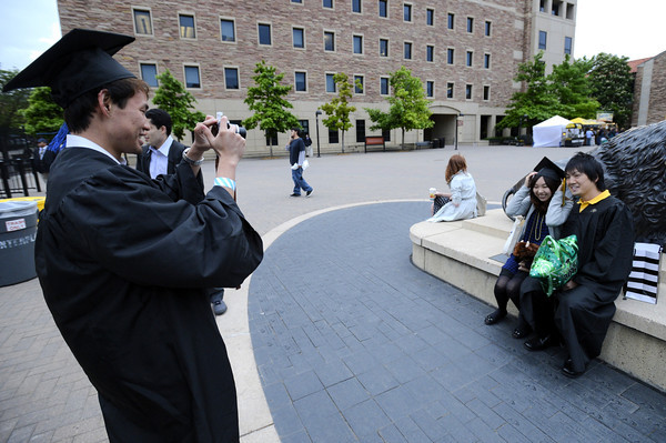 0511CUGRAD1.jpg Eddie Shigeta, graduate in international business, takes a photo of Yukihiro Uchida (right), graduate in marketing, and Asuka Ito (middle) next to the buffalo outside Folsum Field prior to the start CU's spring graduation ceremony at the University of Colorado in Boulder, Colorado May 11, 2012. CAMERA/ MARK Leffingwell