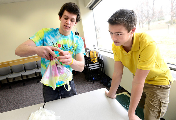 "Philippe Guegan, of CU Teach, at left,  demonstrates a way to make a pattern on a tie dye t-shirt to Tyler Walls,  a 7th-grader at Prospect Ridge Academy in Broomfield, as part of  Engineers Week at IBM's Boulder campus on Tuesday morning February 19, 2013.<br /> The CU Teach program is a four-year degree/licensure program that allows students to complete an education in a mathematics or science major and fulfill the requirements for a Colorado initial teaching license in Secondary Mathematics or Secondary Science.<br /> For more photos go to  <a href=""http://www.coloradodaily.com"">http://www.coloradodaily.com</a><br /> Photos by Paul Aiken"
