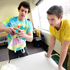 """Philippe Guegan, of CU Teach, at left,  demonstrates a way to make a pattern on a tie dye t-shirt to Tyler Walls,  a 7th-grader at Prospect Ridge Academy in Broomfield, as part of  Engineers Week at IBM's Boulder campus on Tuesday morning February 19, 2013.<br /> The CU Teach program is a four-year degree/licensure program that allows students to complete an education in a mathematics or science major and fulfill the requirements for a Colorado initial teaching license in Secondary Mathematics or Secondary Science.<br /> For more photos go to  <a href=""""http://www.coloradodaily.com"""">http://www.coloradodaily.com</a><br /> Photos by Paul Aiken"""