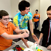 "Philippe Guegan, of CU Teach, center, gives suggestions about how to tie dye a t-shirt to Coby Hsin,  a 7th-grader at Prospect Ridge Academy in Broomfield, as part of  Engineers Week at IBM's Boulder campus on Tuesday morning February 19, 2013. With Hsin is Jacob Boyer at left.<br /> The CU Teach program is a four-year degree/licensure program that allows students to complete an education in a mathematics or science major and fulfill the requirements for a Colorado initial teaching license in Secondary Mathematics or Secondary Science.<br /> For more photos go to  <a href=""http://www.coloradodaily.com"">http://www.coloradodaily.com</a><br /> Photos by Paul Aiken"