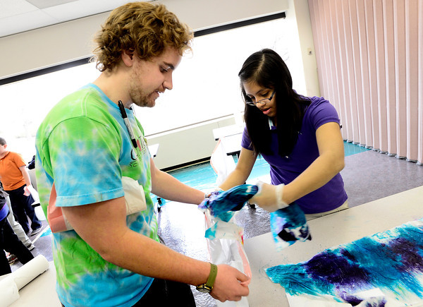 """Caleb Ulliman, of CU Teach works with Araceli Silva, 7th grader at Prospect Ridge Academy at Broomfield, to bag up her tie-dyed t-shirt during  Engineers Week at IBM's Boulder campus on Tuesday morning February 19, 2013.<br /> The CU Teach program is a four-year degree/licensure program that allows students to complete an education in a mathematics or science major and fulfill the requirements for a Colorado initial teaching license in Secondary Mathematics or Secondary Science.<br /> For more photos go to  <a href=""""http://www.coloradodaily.com"""">http://www.coloradodaily.com</a><br /> Photos by Paul Aiken"""