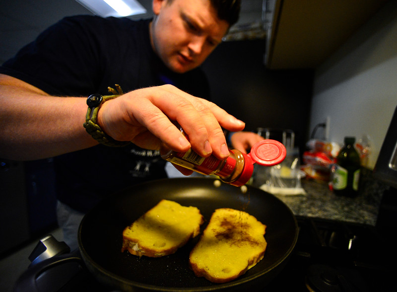 KRISTOPHER RADDER - BRATTLEBORO REFORMER<br /> Brattleboro Police Det. Ryan Washburn sprinkles some cinnamon on top of French toast.