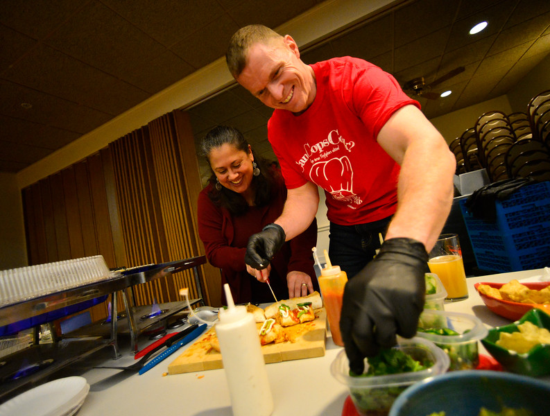 KRISTOPHER RADDER — BRATTLEBORO REFORMER<br /> Michael Heiden, a Brattleboro Firefighter, and his wife prepare a dish during the 4th annual Can Cops Cook fundraiser at the American Legion, in Brattleboro, on Saturday, Jan. 26, 2019.