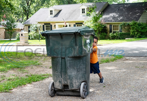Carson Howard, 3, returns his family's empty trashcan to the house from the curb after pickup on Tuesday, June 30, 2020. Howard loves trash trucks, including toys and the real thing. He likes to return his neighbors' empty cans from the street twice a week.