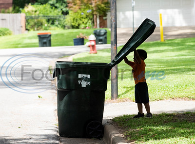 Carson Howard, 3, closes the lid on his neighbor's empty trash can after trash pickup in Tyler on Tuesday, June 30, 2020. Howard loves trash trucks, including toys and the real thing. He likes to return his neighbors' empty cans from the street twice a week.