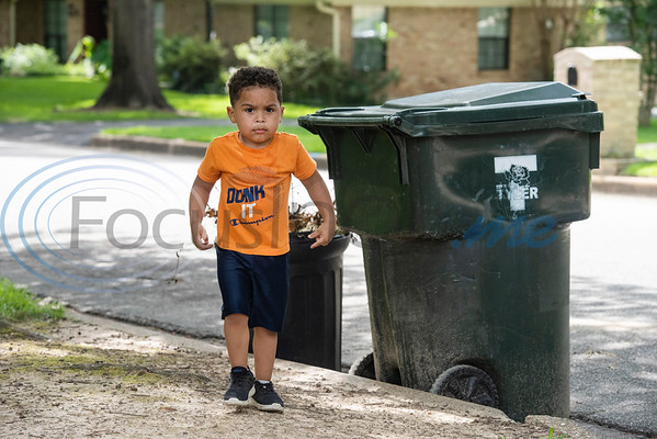 Carson Howard, 3, closes the a trash can lid after the wind blew it open as he played outside waiting for the the trash truck to drive by his house in Tyler on Tuesday, June 30, 2020. Howard loves trash trucks, including toys and the real thing. He likes to return his neighbors' empty cans from the street twice a week.