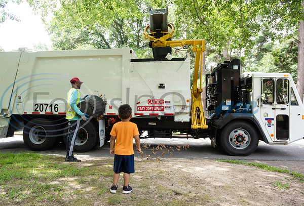 Carson Howard, 3, watches as a City of Tyler trash crew empties his family's trash cans on Tuesday, June 30, 2020. Howard loves trash trucks, including toys and the real thing. He likes to return his neighbors' empty cans from the street twice a week.