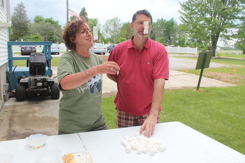 HALEE HEIRONIMUS / GAZETTE Dana Massimino, right, and Greg Johnson, left, participate in a marshmallow-stacking competition during the National Cancer Survivors Day celebration.