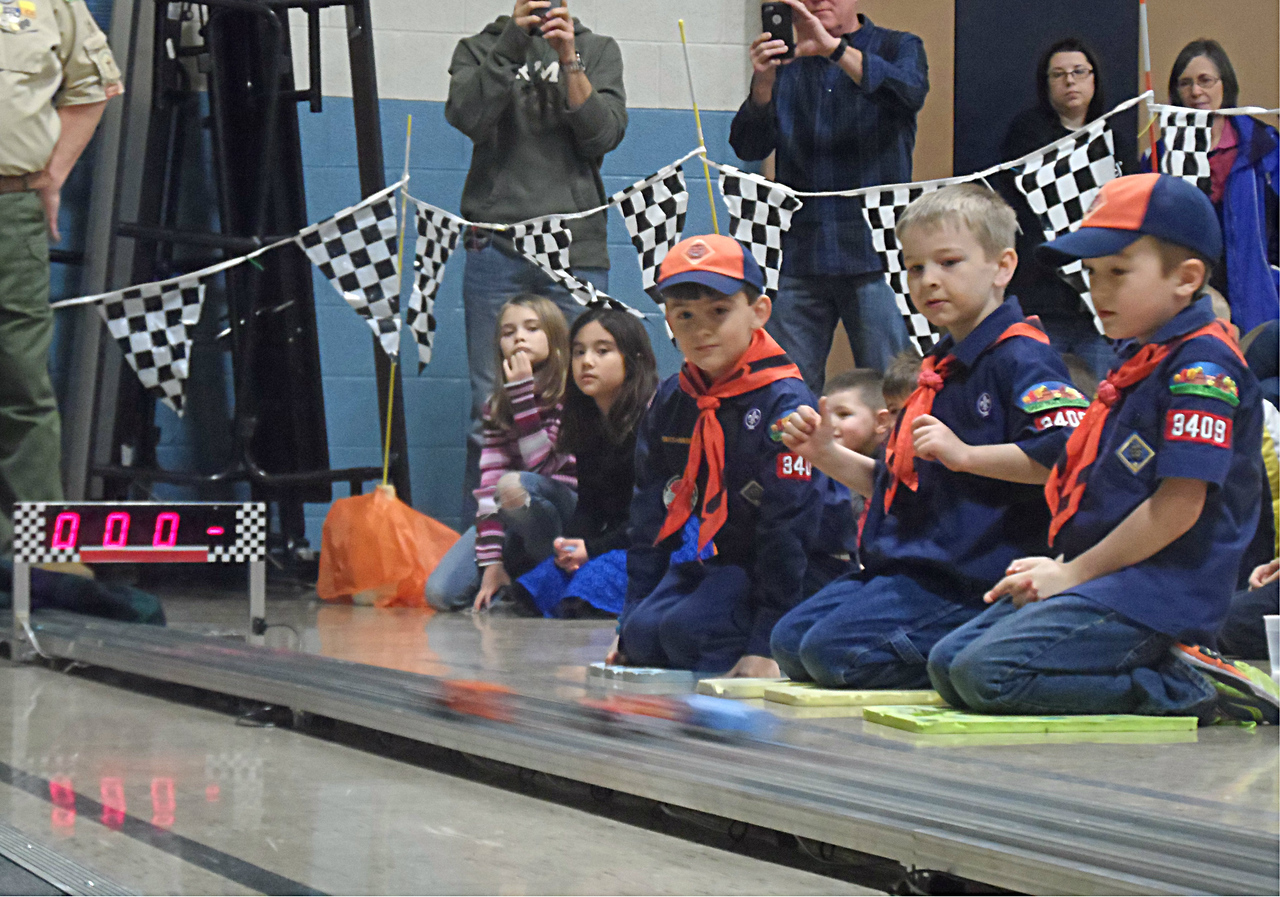 PHOTO PROVIDED Cub Scouts and family members watch with anticipation in the Pinewood Derby car race event held Saturday at Crestview Elementary School in Brunswick.