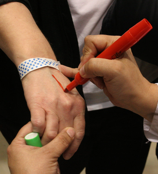 As the voters would leave the voting booth, an official would mark the back of hands to show that they had voted.