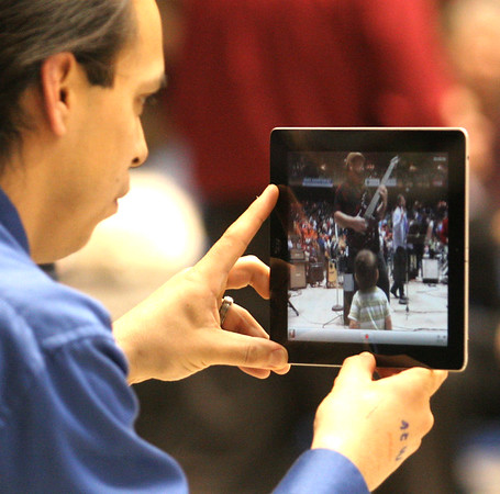 Anthony Martinez uses his iPod to film his son dancing to the live music during the Boise, Idaho caucus.