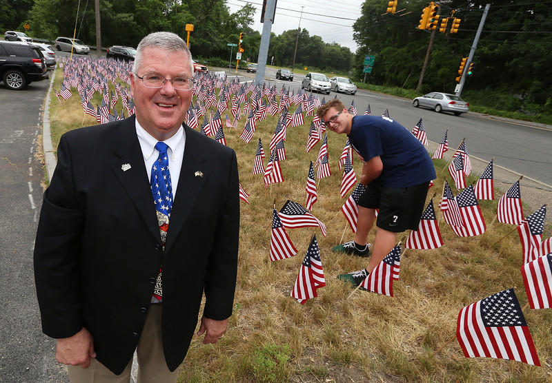 LAER Realty agent partner Jon Crandall and his son Tim Crandall, both of Dunstable, with some of the 700 American flags now on the property. They straighten any tilting ones every day. (SUN/Julia Malakie)