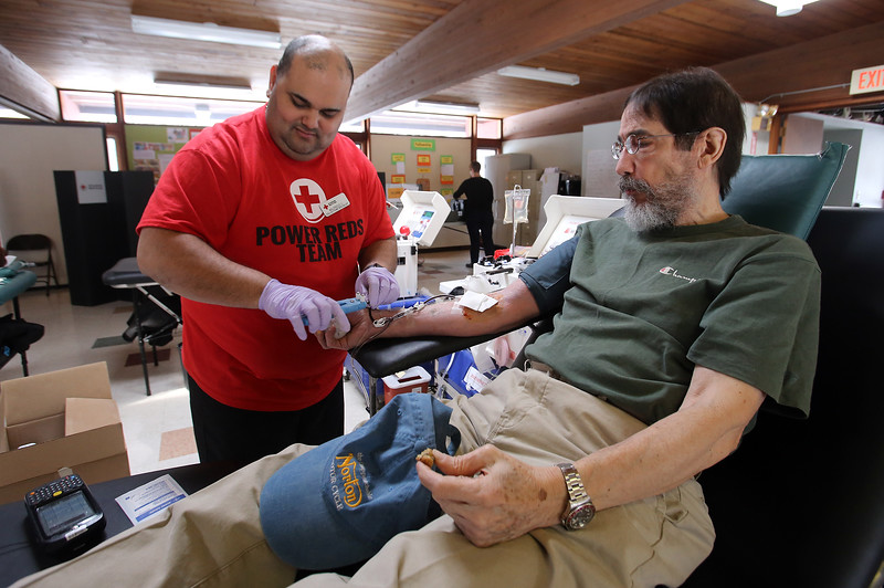 """Regular blood donor David Mercado of Lowell eats cookies as he donates """"double reds"""" - twice the number of red blood cells, with the rest of his blood being returned to his system, at a Red Cross blood drive at Trinity Lutheran Church in Chelmsford. Red Cross collections specialist if Wilfredo Cruz of Lawrence.  (SUN/Julia Malakie)"""
