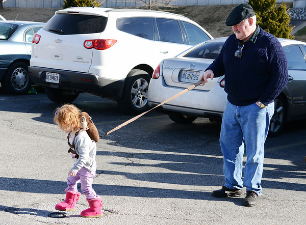"""""""The Chain of Command"""" or """"Leash Law""""<br /> Rick Boyd of Oronogo holds tight to a child leash as his 2-year-old granddaughter Peyton Adamson of Webb City pulls against him as she walks around the Joplin Family Y South parking lot Wednesday morning, Jan. 1, 2014. The family was there for the Chilly Challenge 5K run.<br /> Globe 