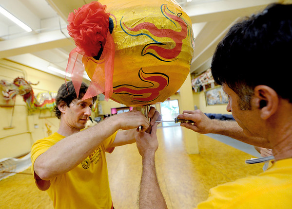 "Dave Spielman, left, and Shifu Howie Solow, work on the ""pearl or teaser,"" that entices the dragon.<br /> Students of the Shaolin Hung Mei Kung Fu Academy in Boulder  assembled a 75-foot dragon in advance of the Colorado Dragon Boat Festival at the end of July.<br /> For more photos and a video of the assembly, go to  <a href=""http://www.dailycamera.com"">http://www.dailycamera.com</a>.<br /> Cliff Grassmick / July 7, 2012"