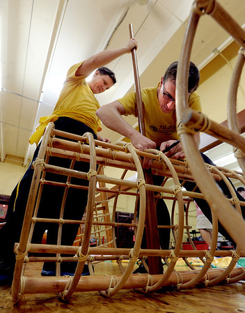 """Oliver DeWolfe, left, and Brandon Rachal, assemble the skeleton of the new dragon.<br /> Students of the Shaolin Hung Mei Kung Fu Academy in Boulder  assembled a 75-foot dragon in advance of the Colorado Dragon Boat Festival at the end of July.<br /> For more photos and a video of the assembly, go to  <a href=""""http://www.dailycamera.com"""">http://www.dailycamera.com</a>.<br /> Cliff Grassmick / July 7, 2012"""