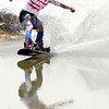 "Tanar Nobles, of Avon, is reflected in the pond as he skims across on his snowboard on Friday, July 1, at Arapahoe Basin Ski Resort in Summit County. For a video of the ski day go to  <a href=""http://www.dailycamera.com"">http://www.dailycamera.com</a><br /> Jeremy Papasso/ Camera"