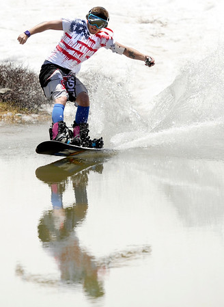 """Tanar Nobles, of Avon, is reflected in the pond as he skims across on his snowboard on Friday, July 1, at Arapahoe Basin Ski Resort in Summit County. For a video of the ski day go to  <a href=""""http://www.dailycamera.com"""">http://www.dailycamera.com</a><br /> Jeremy Papasso/ Camera"""