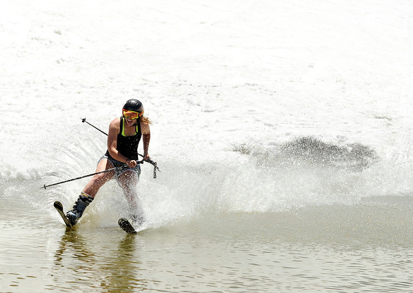 """Carolyn Brent, of Boulder, skims across the pond on her snow skis on Friday, July 1, at Arapahoe Basin Ski Resort in Summit County. For a video of the ski day go to  <a href=""""http://www.dailycamera.com"""">http://www.dailycamera.com</a><br /> Jeremy Papasso/ Camera"""