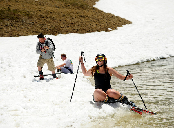"""Carolyn Brent, of Boulder, struggles to get out of the freezing water after falling while attempting to skim across a pond with her snow skis on Friday, July 1, at Arapahoe Basin Ski Resort in Summit County. For a video of the ski day go to  <a href=""""http://www.dailycamera.com"""">http://www.dailycamera.com</a><br /> Jeremy Papasso/ Camera"""