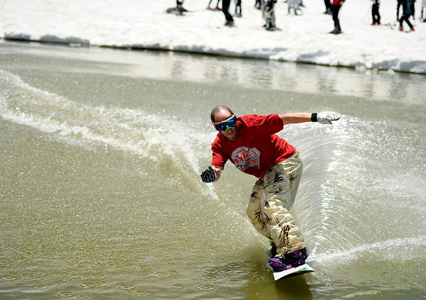 """Howard Green, of Edwards, skims across the pond in style while snowboarding on Friday, July 1, at Arapahoe Basin Ski Resort in Summit County. For a video of the ski day go to  <a href=""""http://www.dailycamera.com"""">http://www.dailycamera.com</a><br /> Jeremy Papasso/ Camera"""