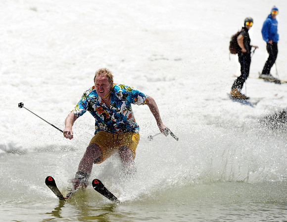 "Doug Brent, of Boulder, left, makes an attempt at skimming the pond midway up the mountain on Friday, July 1, at Arapahoe Basin Ski Resort in Summit County.  For a video of the summer ski day go to  <a href=""http://www.dailycamera.com"">http://www.dailycamera.com</a><br /> Jeremy Papasso/ Camera"