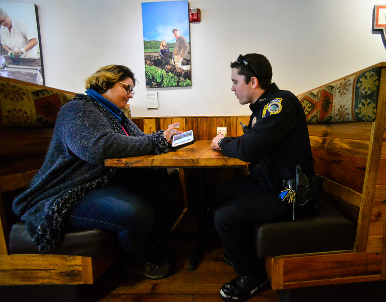 KRISTOPHER RADDER — BRATTLEBORO REFORMER<br /> Olivia Brisson shares a video with Dave Lockerby, a Brattleboro police officer, during a Coffee with a Cop event at The Works, in Brattleboro, on Wednesday, Dec. 18, 2019.