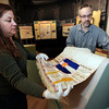 "Curator Julie Schumaker, left, and exhibit designer Seth Frankel place a historic Woman's Christian Temperance Union table runner on a stand on Monday, Feb. 26, at the beer history exhibit at the Boulder History Museum in Boulder. For a video about the exhibit go to  <a href=""http://www.dailycamera.com"">http://www.dailycamera.com</a><br /> Jeremy Papasso/ Camera"