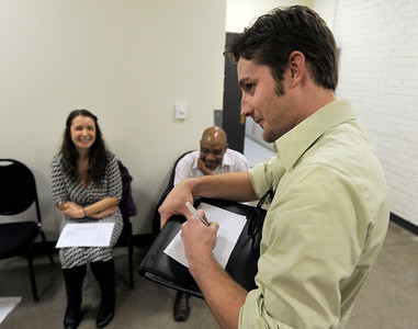 Sean Scrutchins, of Denver, at right, fills out his audition paperwork in front of Lanie Nocack, of Longmont, left, and Cris Davenport, of Denver, during an audition for the Colorado Shakespeare Festival on Friday, Jan. 18, at the Denver Performing Arts Tramway building in Denver. For more photos and video of the audition go to www.dailycamera.com Jeremy Papasso/ Camera