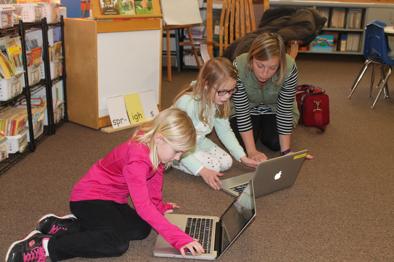 LAWRENCE PANTAGES / GAZETTE Jolene Speckman, a second-grade teacher at Ella Canavan Elementary School in Medina, works with Alayna Schefft, 7 (left), and Tinsley Van Deriest, 7, on a computer project researching Native Americans. Speckman, who has taught at Canavan for 11 years, said the students will make their presentations to the class today.
