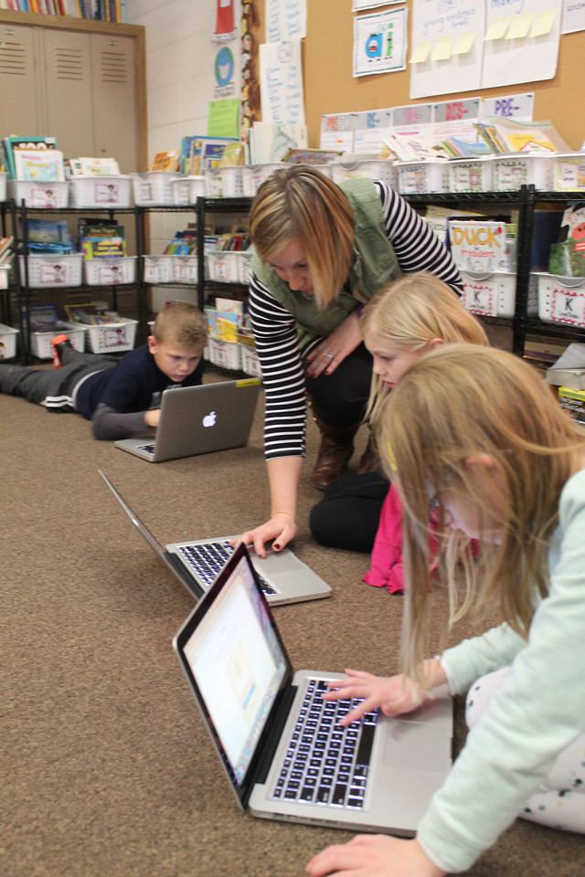 "LAWRENCE PANTAGES / GAZETTE Ella Canavan Elementary School second-grade teacher Jolene Speckman works with Alayna Schefft, 7, on Wednesday on a computer research project on Native American life. At left is Syler Teubner, 8, and at right is Tinsley Van Deriest, 7. Speckman said the students are scheduled to present their projects to the class today. The computers are part of an education curriculum called ""problem-based learning."""