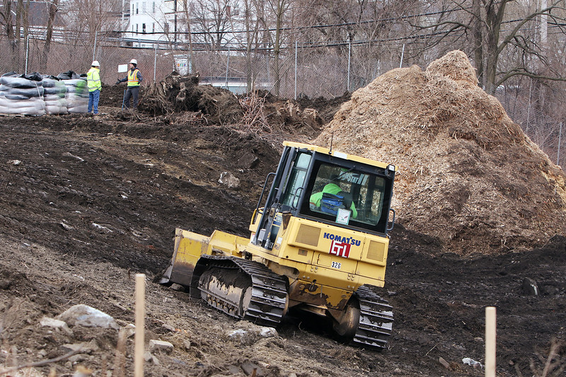Lord Overpass reconstruction project continues. Topsoil is being moved into a pile to be conserved for late use. The pile of woodchips from chipped trees will go to an energy plant. (SUN/Julia Malakie)