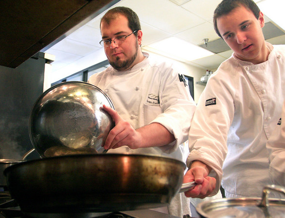 Ivan Caballero (left) and Codi Siegried prepare dishes during their farm to table cooking class at the Culinary School of the Rockies in Boulder on Thursday, July 15.<br /> Greg Lindstrom / The Camera
