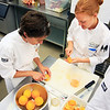 Chris McCluskey (left) and Lauren Limbird peel and slice oranges during their farm to table cooking class at the Culinary School of the Rockies in Boulder on Thursday, July 15.<br /> Greg Lindstrom / The Camera